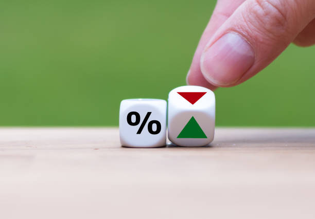 hand is turning a dice and changes the direction of an arrow symbolizing that the interest rates are going down (or vice versa) - interest rate stock photos and pictures