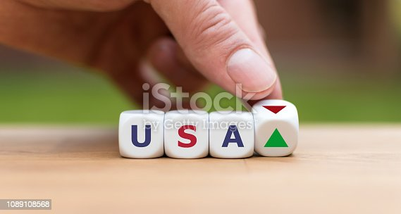 Hand is turning a dice and changes the direction of an arrow symbolizing that US economy is changing the trend and goes up instead of down (or vice versa)