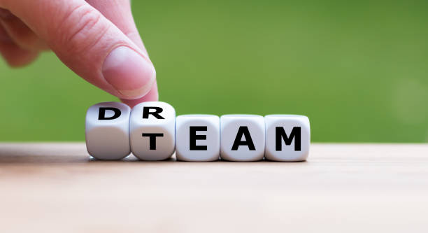 "hand is turning a dice and changes the word ""dream"" to ""team"" - group of people стоковые фото и изображения"