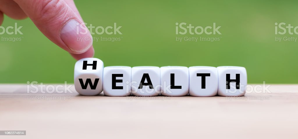 "Hand is turning a dice and changes the word ""Health"" to ""Wealth"" royalty-free stock photo"