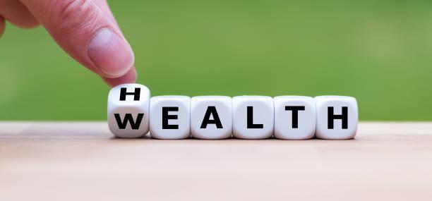 """手正在變成一個骰子, 把 """"健康"""" 這個詞變成 """"財富"""" """" - 財富 個照片及圖片檔"""