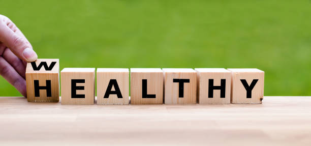 """mano está convirtiendo un dado y cambia la palabra """"saludable"""" a """"rico"""" - bienestar fotografías e imágenes de stock"""
