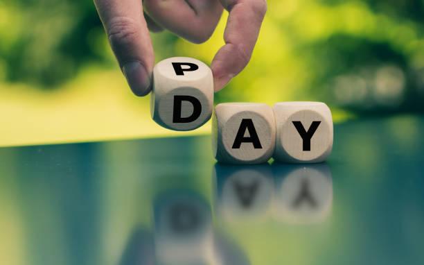 hand dreht einen würfel und ändert das wort pay to day. - gehaltsstreifen stock-fotos und bilder