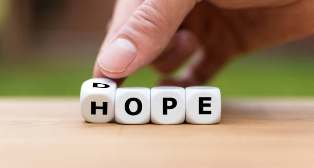 Hand is turning a dice as symbol to have hope instead of dope Hand is turning a dice as symbol to have hope instead of dope drug rehab stock pictures, royalty-free photos & images