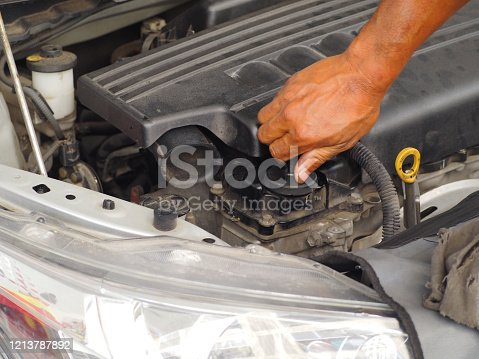 1073743202 istock photo Hand is twisting the engine oil cap.Car maintenance technician He is checking the auto engine, car inspection center. 1213787892