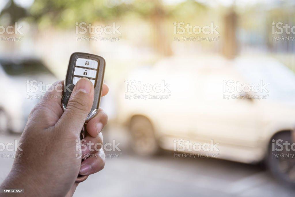 hand låsa upp bilen från fjärrkontrollen i parkering. - Royaltyfri Alarm Bildbanksbilder