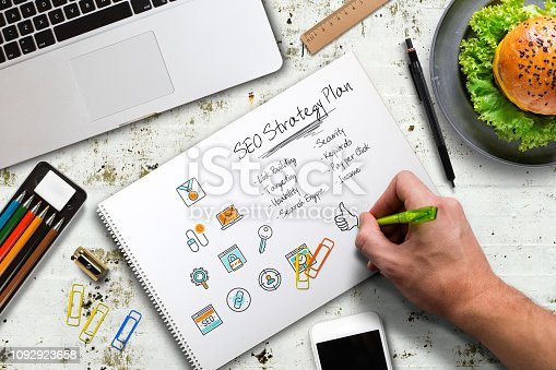 1132786150 istock photo hand is writing a SEO strategy at a computer workplace 1092923658