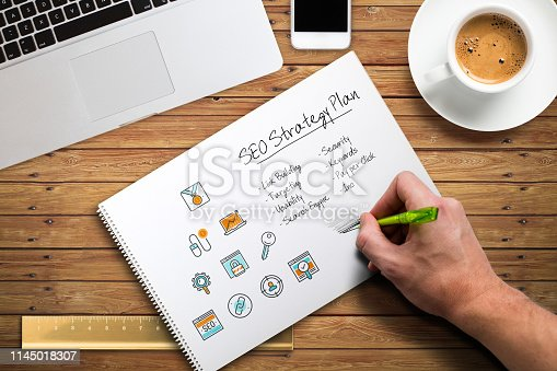 1132786150 istock photo hand is writing a SEO strategy at a computer workplace 1145018307