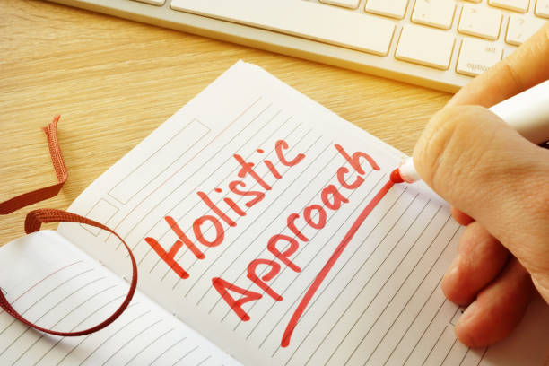 hand is writing holistic approach in the note. - holistic medicine stock photos and pictures