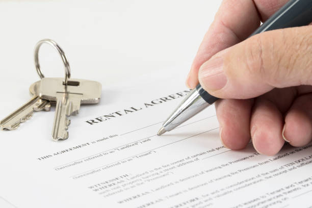 hand is writing with a pen on a rental agreement document, house keys in the background - tenant stock photos and pictures