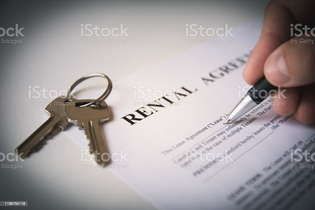 Hand is writing with a pen on a rental agreement document, house keys...