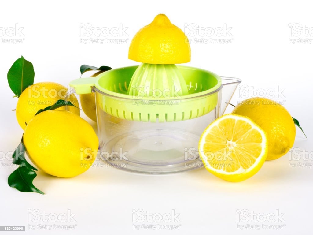 Hand juicer and lemons with green leaves over white background stock photo