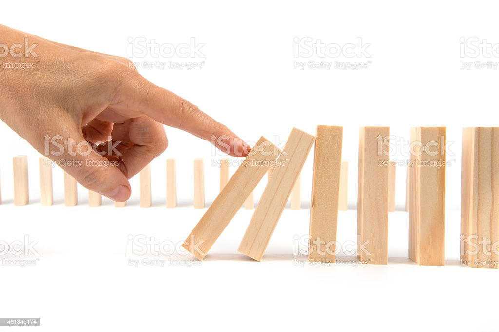 Hand kicking Domino pieces standing in a row for cascade stock photo