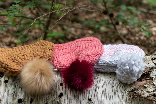 Hand knit pompom hats with forest woodland background