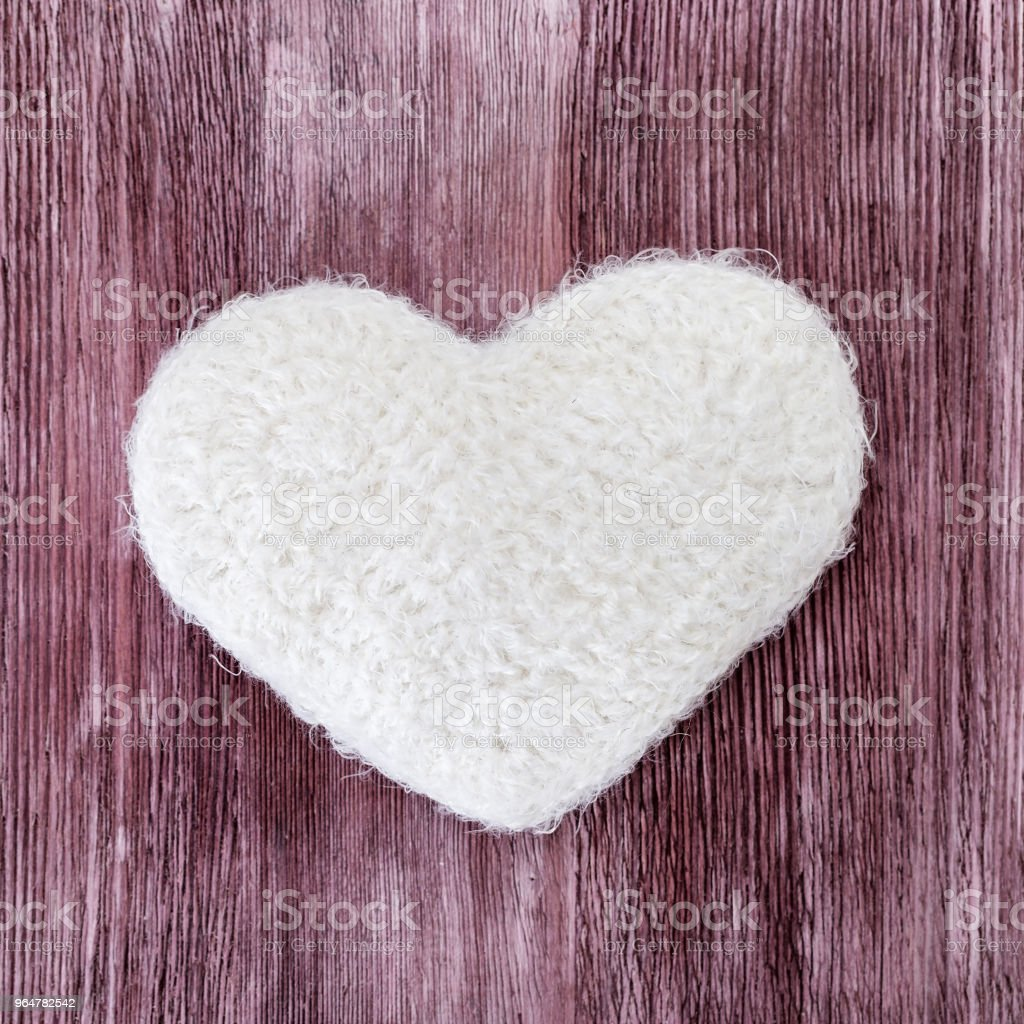 Hand knitted white heart on a wood royalty-free stock photo