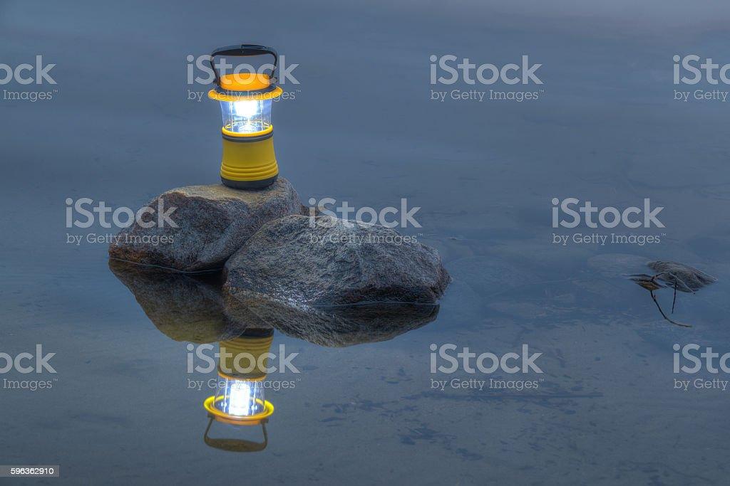 Hand lantern on rock in lake royalty-free stock photo