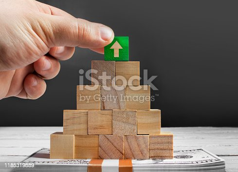 Photo of a male hand laying green wooden cube with arrow on top of wooden pyramid standing on a pack of dollars, depicting successful management.