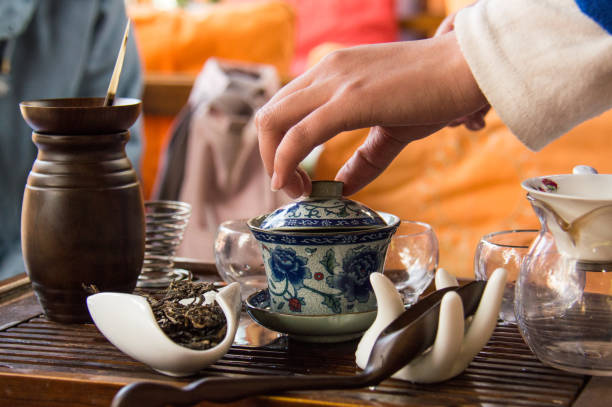 Hand lifting the lid from a teapot in a Lijiang, Yunnan, China teahouse. A tea ceremony with Puer tea in Lijiang, China. A female hand lifts the lid from a blue and white teapot. tea room stock pictures, royalty-free photos & images