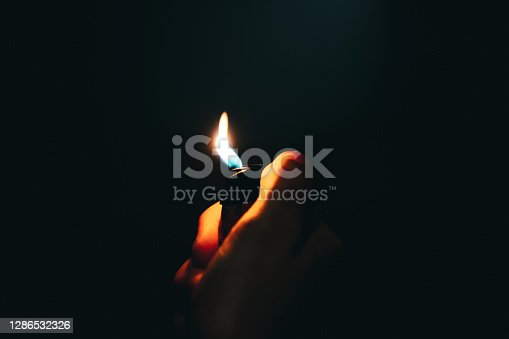 Detail of hand lighting up a cigarette ligher at night. Selective focus on hand and burning flame.
