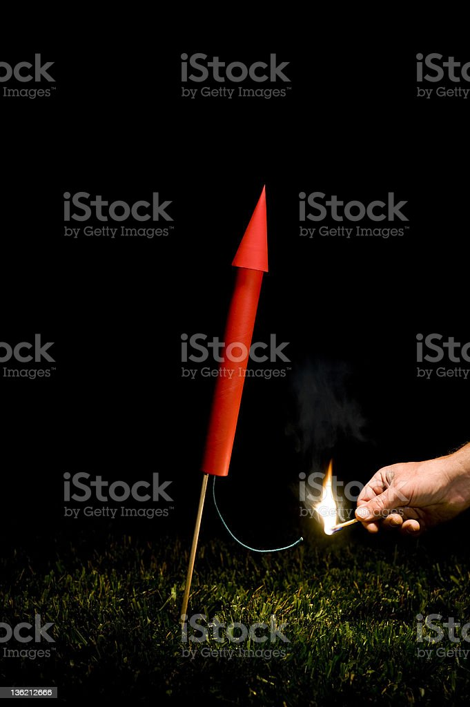 Hand lighting red Rocket/Fireworks fuse stock photo
