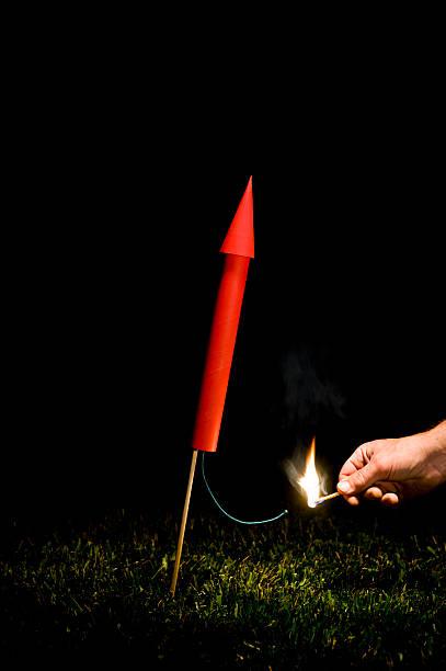 hand lighting red rocket/fireworks fuse - hand tänder ett ljus bildbanksfoton och bilder