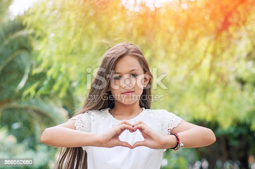 istock Hand love. Pretty little girl showing a heart symbol in the park on warm and sunny summer day. Sunlight effect.  Happy childhood concept. Love symbol. Girl making heart shape with hands. 866552680