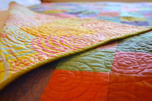 hand made craft quilt folded back - quilt stock photos and pictures