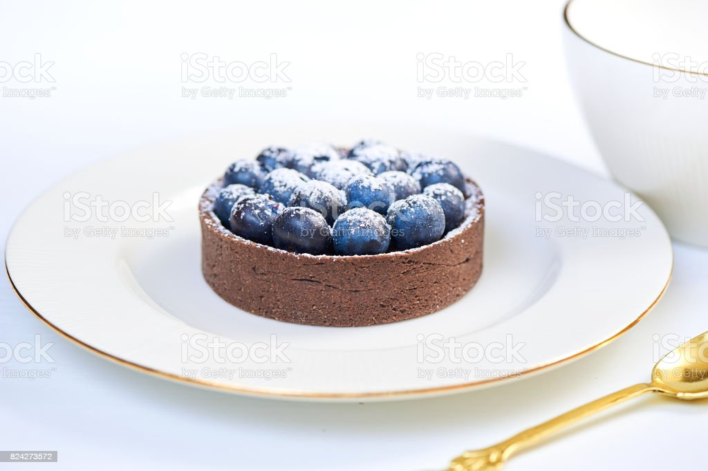 Hand made dessert tarlets from pistachio and chocolaty bakery dough with blueberry decoration served on plate with cap of tea stock photo