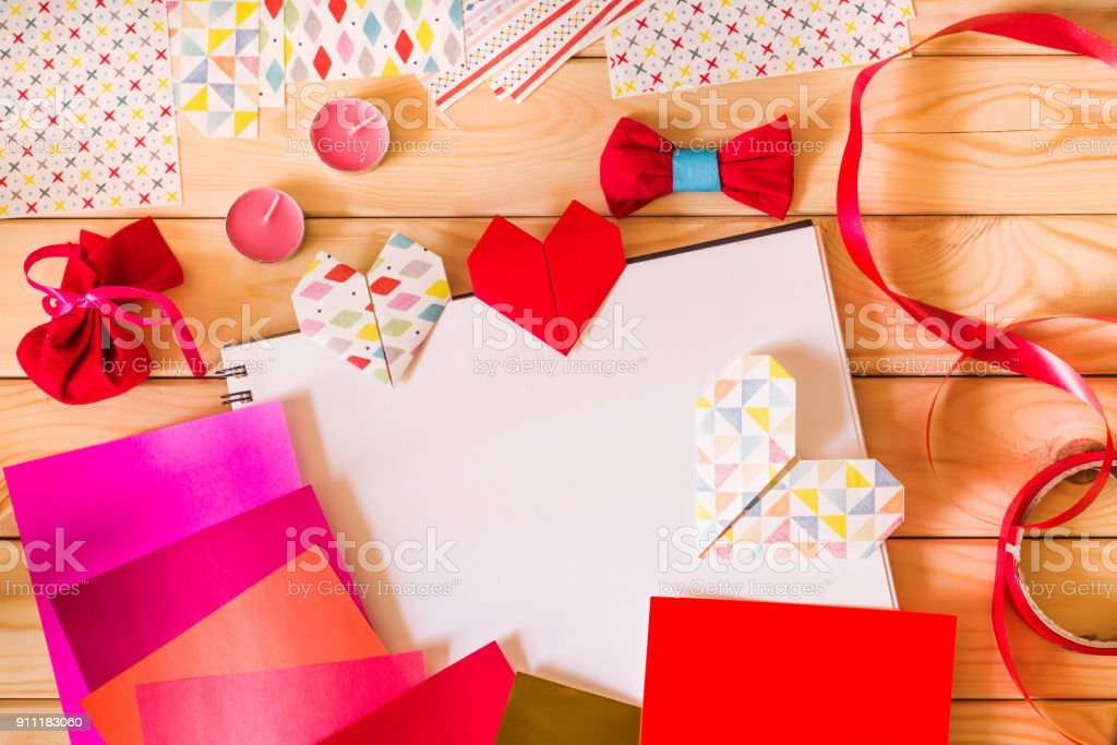 hand made origami paper hearts for valentine's day surrounded by origami paper, candles, gifts stock photo