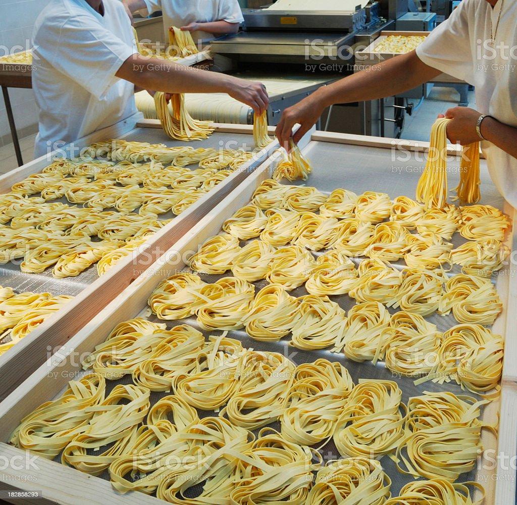 Mano in produzione di tagliatelle, pasta italiana - foto stock