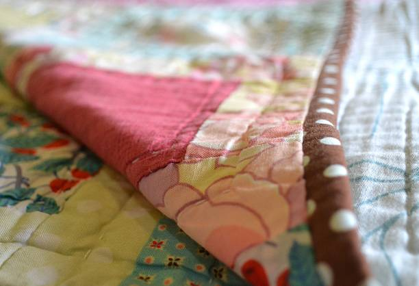 hand made quilt folded back to reveal stitches - quilt stock photos and pictures