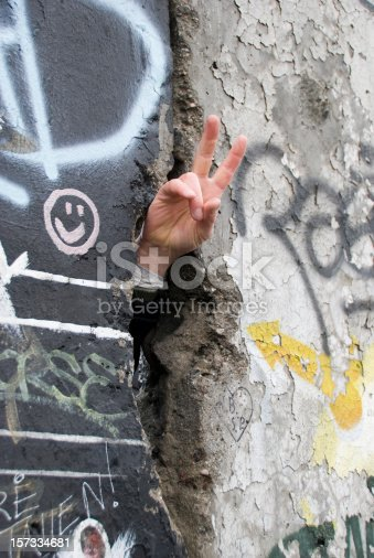 Close up of a hand through a crack in the Berlin Wall, making the PEACE symbol. On the wall graffiti and a smile.