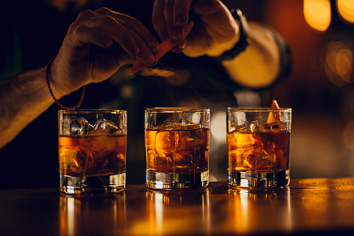 hand making three cocktails on the bar