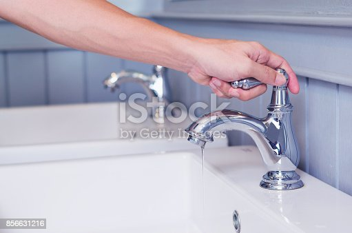 hand man opening silver faucet or water tap with white washing sink in public toilet.