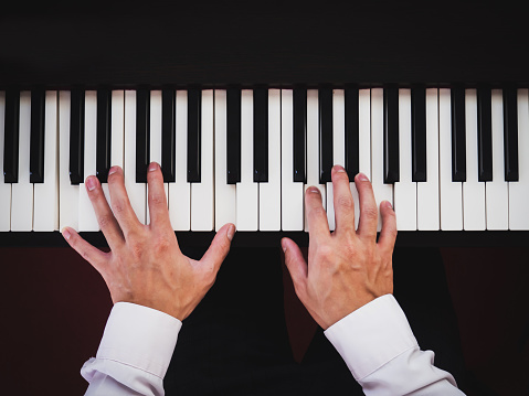 Hand man playing piano. Classical music instrument. Top view.
