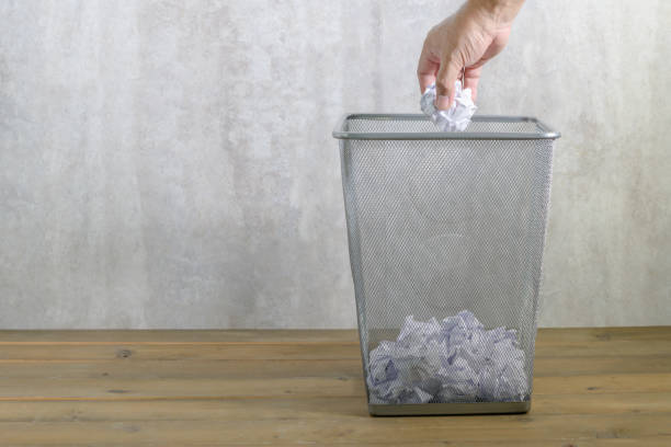 Hand man putting crumpled paper into trash stock photo