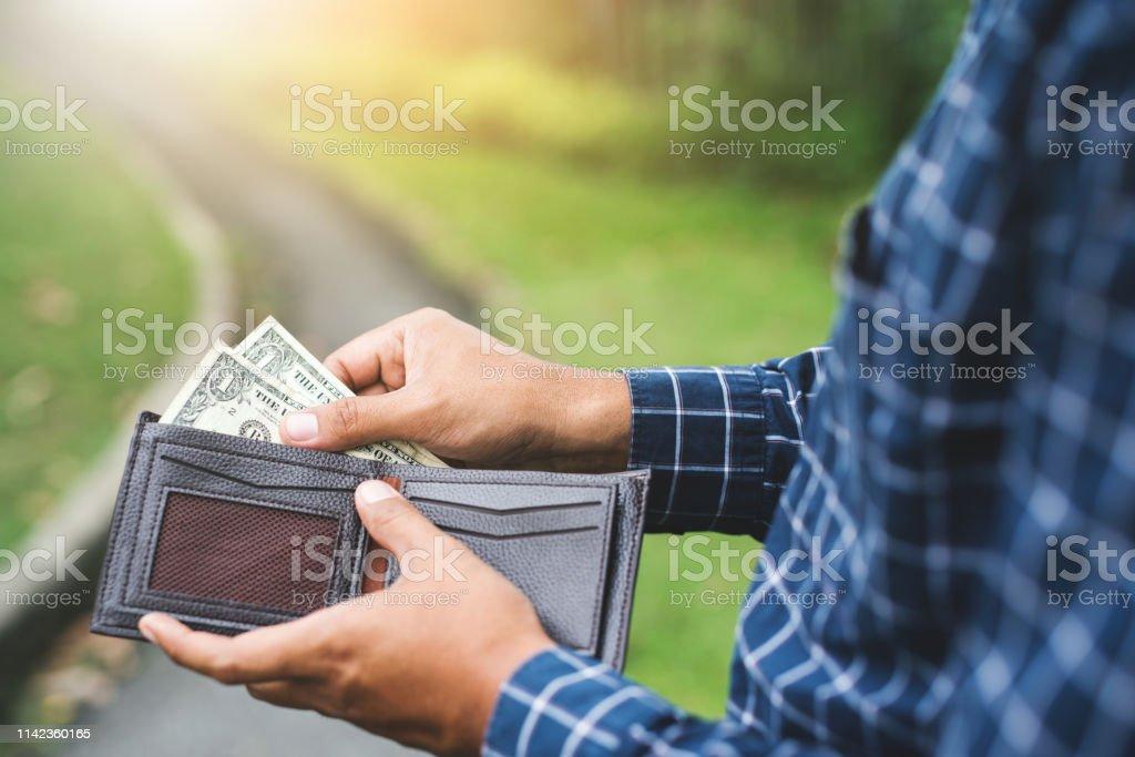 Hand man putting money in wallet.