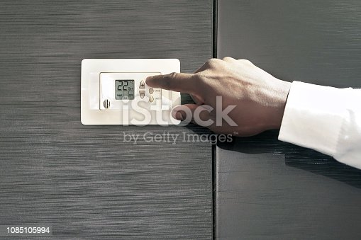 Male hand try to turn on the new air condition in room, in the hotel room. African man hands on the air conditioning control panel. Hand setting temperature air condition.