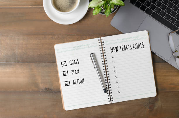 Hand man writing New year's goals on note paper stock photo