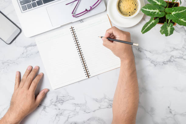 hand man writing on blank notebook with laptop and coffee on marble table stock photo