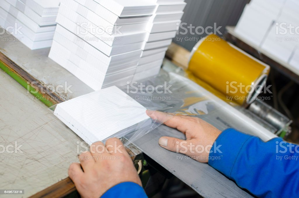 Hand manual work of product packaging in offset print plant stock photo