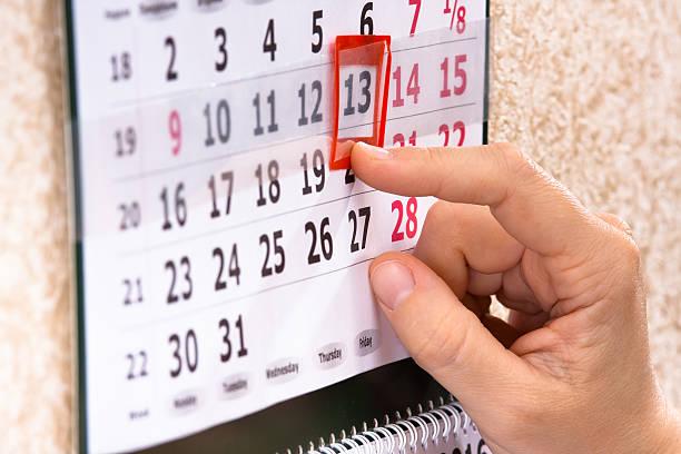 hand marking 13th, friday on calendar stock photo