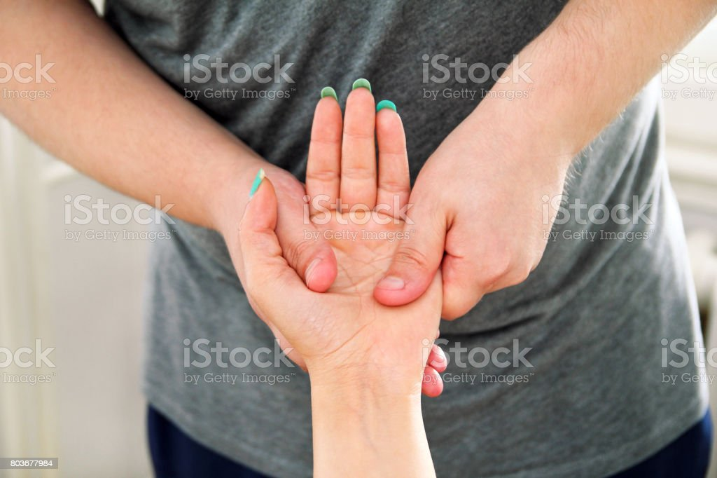 Hand massage. Stroking massage of hands close up. Detail take of a massage session on a hand. Hand massage in the day spa. Body care. A massage therapist giving a hand massage. Massage relax studio. stock photo