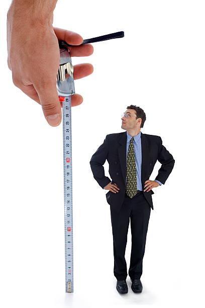 A hand measuring a businessman