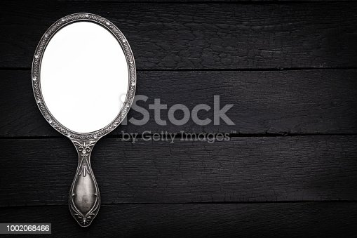 Hand mirror on dark background with space on text