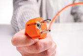 Hand mit Stecker eines Elektrogerätes