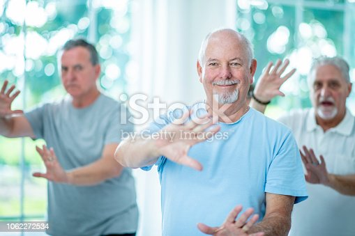 A group of senior men are doing tai chi in a fitness center. They are moving their hands in front of them.