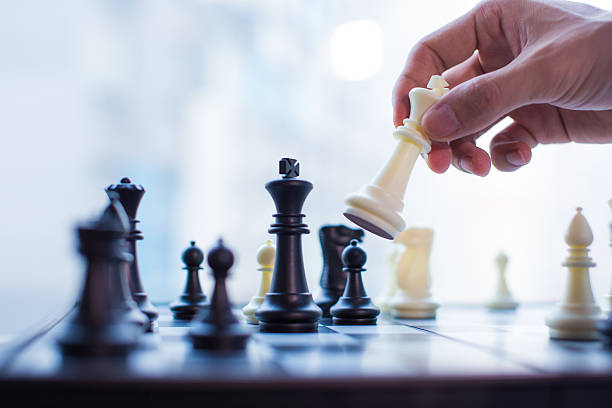 Hand moving the king in chess game stock photo