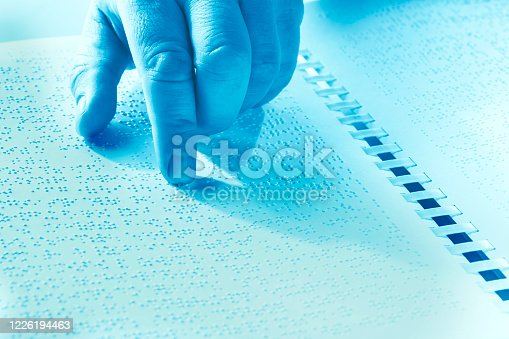 1017945546 istock photo Hand of a blind person reading some braille text touching the relief. Duotone 1226194463