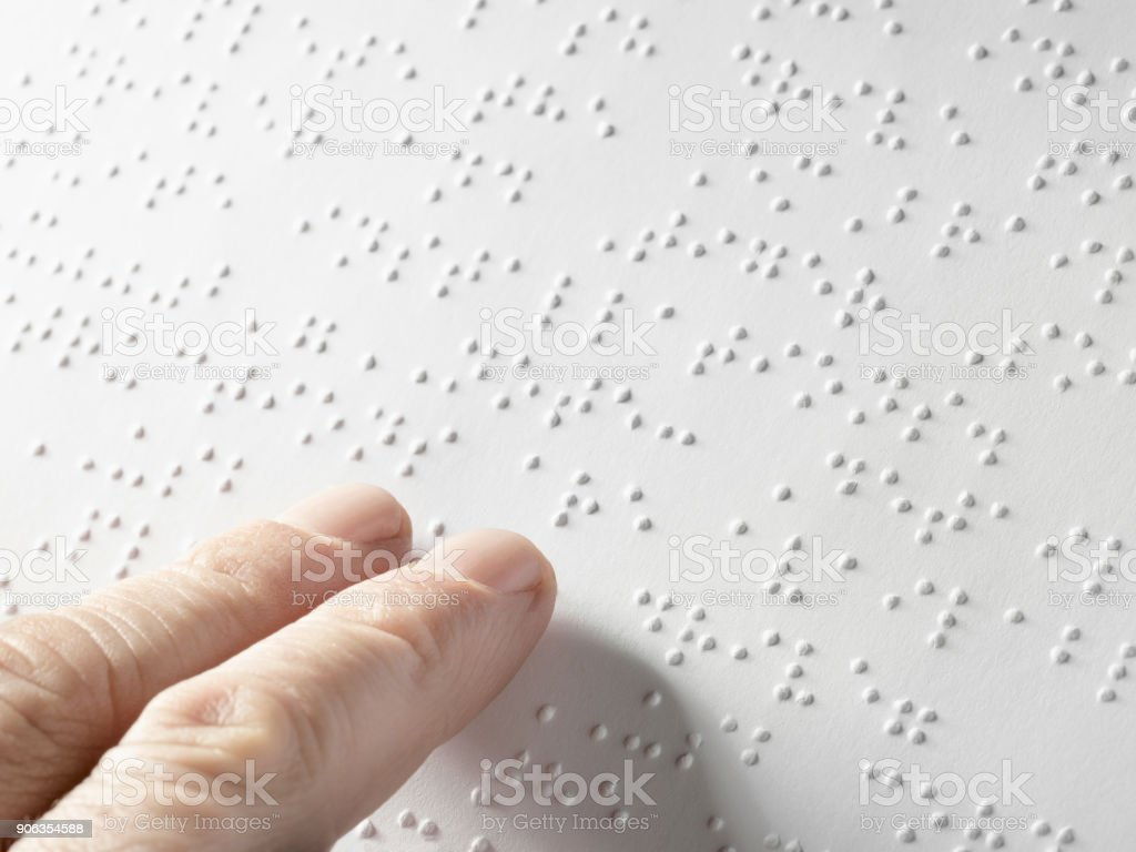 Hand of a blind person reading some braille text touching the relief. Empty copy space for Editor stock photo